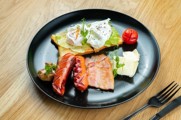 Закройте вверх на яичнице с беконом, сосисками, сыром dor blue на стильной черной плите. еда на завтрак. обслуживание в ресторане. деревянный фон