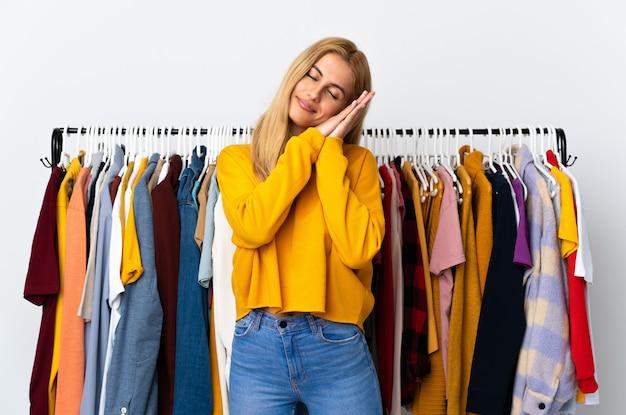 Молодая белокурая женщина в магазине одежды делая жест сна в dorable выражении