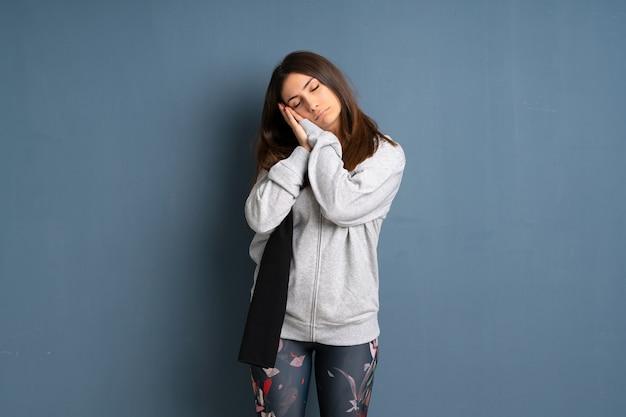 Молодая женщина спорта, делая жест сна в dorable выражении