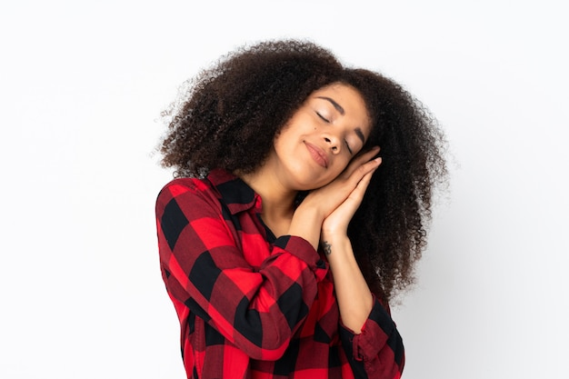 Молодая афро-американская женщина над изолированной стеной делая жест сна в dorable выражении