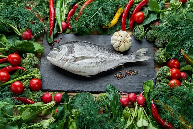 Dorada fish and green vegetables around on old wooden table. top view, healthy food.