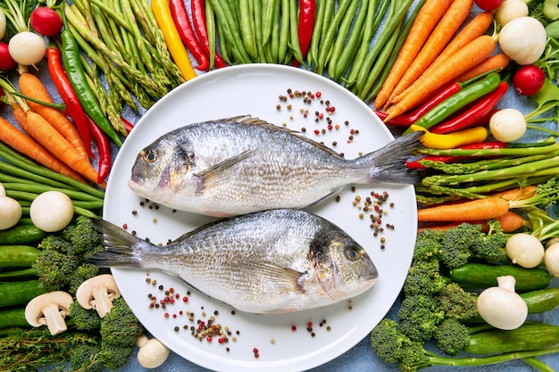 Dorada fish on white dish with colorful vegetables around.
