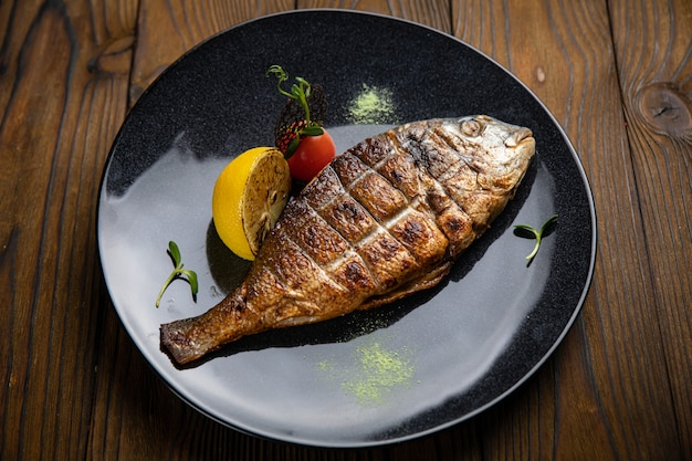 Dorada grilled on plate with vegetables