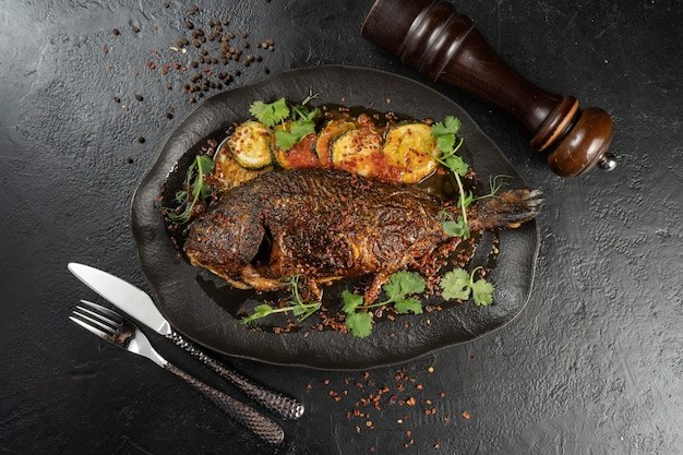 Dorada with fried zucchini. hot main course of sea fish and baked vegetables with microgreens and spices on a beautiful black plate