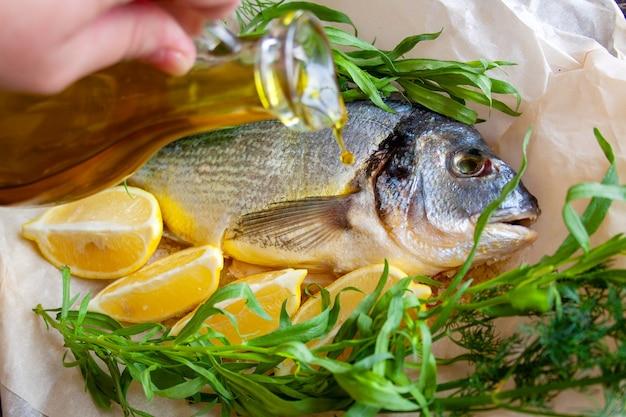 Дорада с лимоном и зеленью, перед запеканием повар поливает рыбу оливковым маслом
