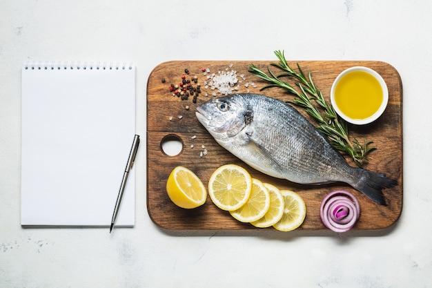 소박한 나무 커팅 보드에 있는 도라도 물고기는 향신료와 조리법 또는 메뉴를 위한 노트북입니다. 흰색 배경에 상위 뷰입니다.