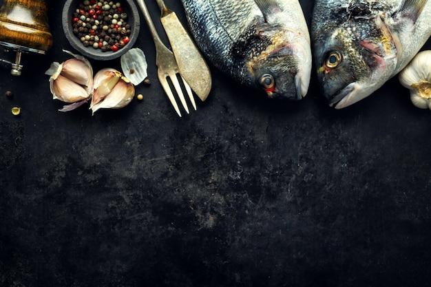 Dorado fish with ingredients on dark