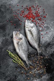 Dorado sea fish. mediterranean cuisine, healthy cooking concept. black background. top view.