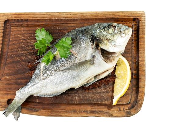 木の板にレモンとハーブを添えたドラド。健康的な食事と食事。白い背景で隔離。テキスト用のスペース。