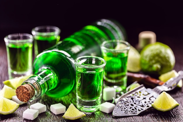 Doses of absinthe with brown sugar cubes. distillate of absinthe in a glass and lemon, stainless steel spoon isolated on black surface