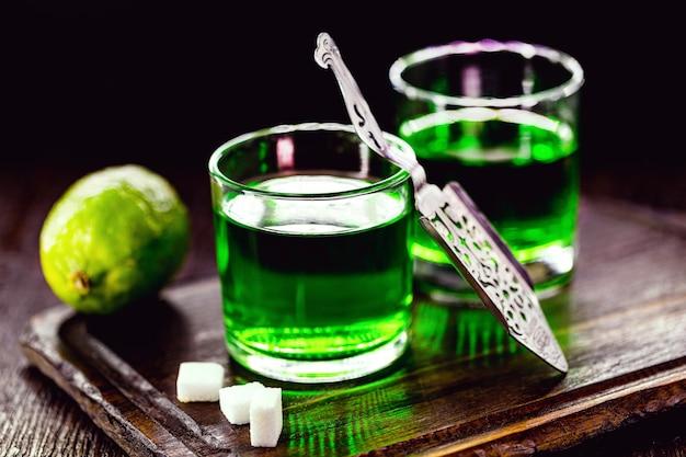 アブサンとブラウンシュガーキューブの投与量。ガラスとレモンのアブサンの留出物、黒い表面に分離されたステンレス鋼のスプーン