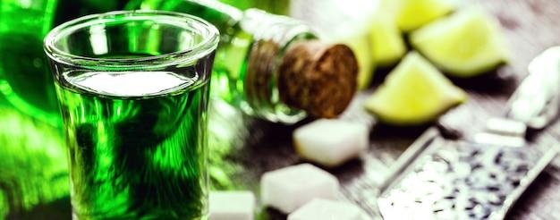角砂糖を含むアブサンの投与量。アブサンボトル、緑色の蒸留飲料
