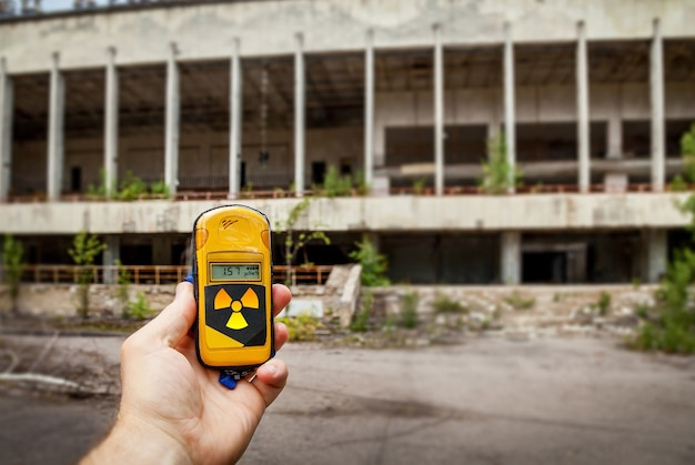 A dosimeter in hands with a level of radioactivity in the city of pripyat, a ghost town of the chernobyl nuclear power plant affected by a nuclear disaster in 1986, chernobyl exclusion zone, ukraine.