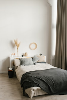 Double bed in the bedroom in gray and white shades. scandinavian home interior