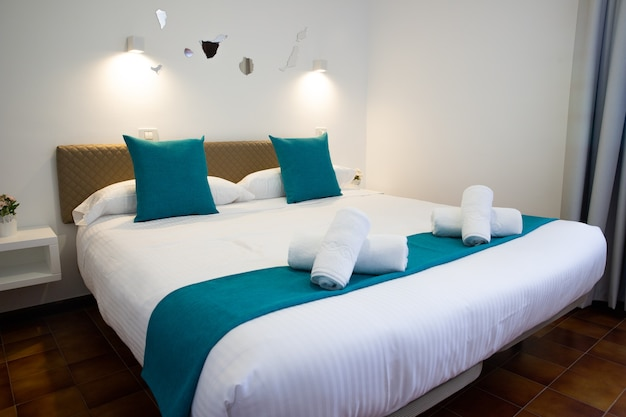 Double bed with the folded towels on top, inside a bedroom.