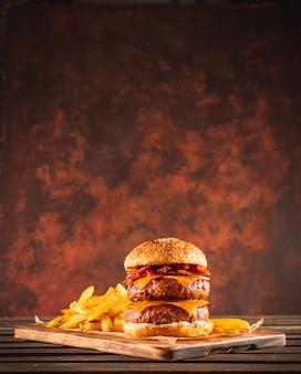 Двойной бургер из говядины и бекона с сыром чеддер и чипсами на деревянной доске
