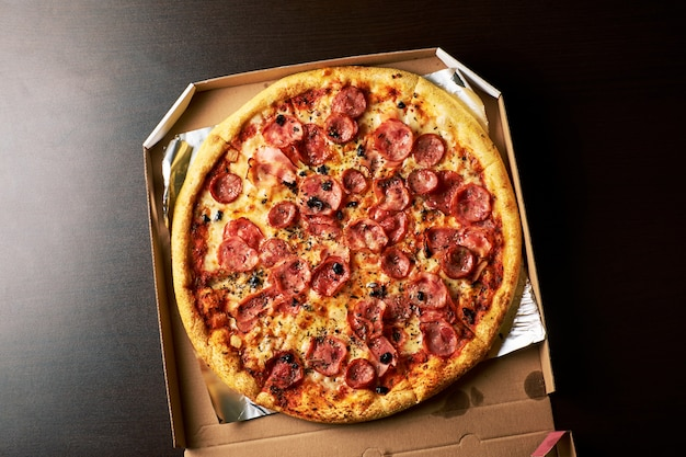 Double cheese pizza from whole pizza in a cardboard box dark table background.