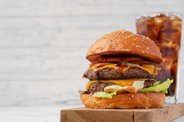 Двойной чизбургер на деревянной доске на белом размытом фоне