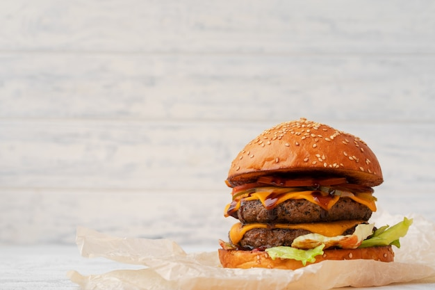 Double cheeseburger served on wooden board against white blurred background