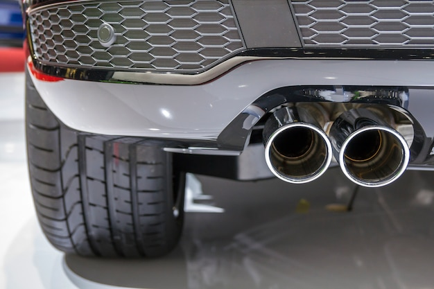 Double chrome exhaust pipe of powerful sport car with grey plastic details