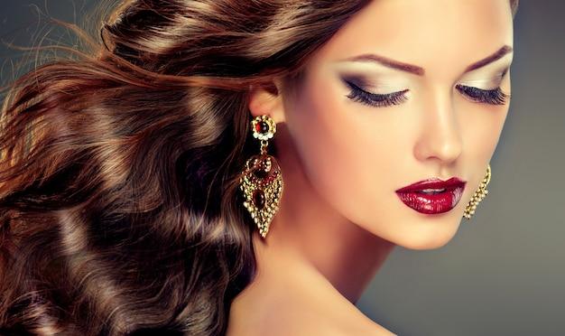 이중 색깔의 닫힌 눈꺼풀과 밝은 빨간색 립스틱. 얼굴에 우아한 화장과 길고 밀도가 높은 곱슬 머리를 가진 아름 다운 젊은 여자. 헤어 스타일링, 헤어 케어 및 메이크업.
