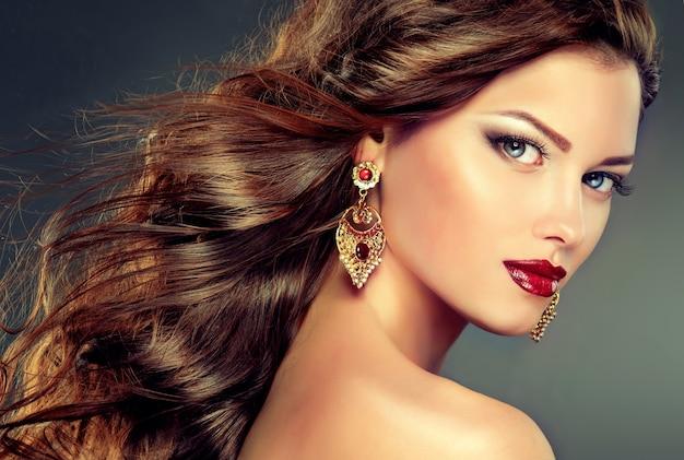 이중 색 눈꺼풀과 밝은 빨간색 립스틱. 아름다운 푸른 눈의 측면 시선. 얼굴에 우아한 화장과 길고 밀도가 높은 곱슬 머리를 가진 젊은 여성. 헤어 스타일링, 헤어 케어 및 메이크업.