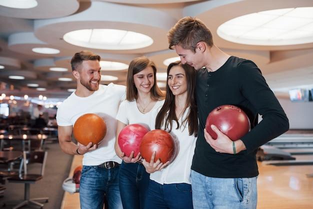 Doppio appuntamento. i giovani amici allegri si divertono al bowling durante i fine settimana