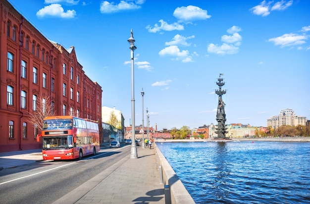 夏の晴れた日にモスクワのモスクワ川にある堤防とピョートル大帝の記念碑にある2階建ての赤いバス