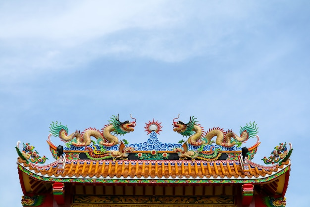 Double dragon on roof of chinese temple gate and blue cloud