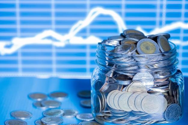 Doppia exporsure impilata di monete e notte con grafico.