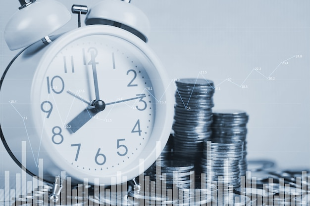 Double exposure of alarm clock and coins stacks with city background