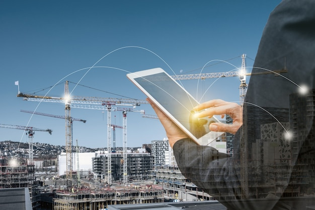 Double exposure businesswoman touching tablet with network line on construction building background