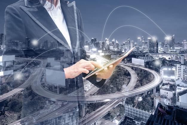 輝く街でネットワークラインとタブレットに触れる二重露光実業家