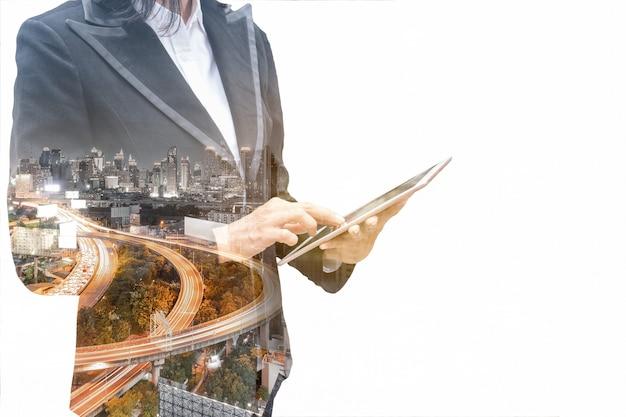 白い背景の街の高速道路のトラフィックとタブレットに触れる二重露光実業家