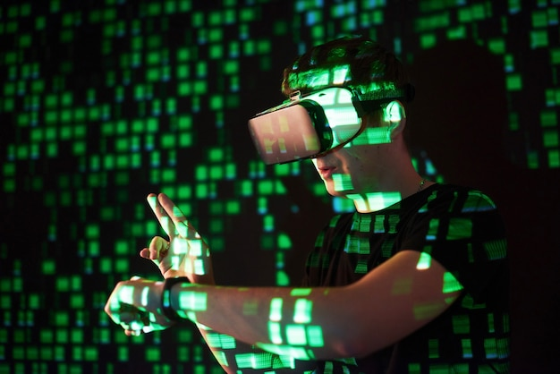Double exposure of a caucasian man and virtual reality vr headset is presumably a gamer or a hacker cracking the code into a secure network or server, with lines of code in green
