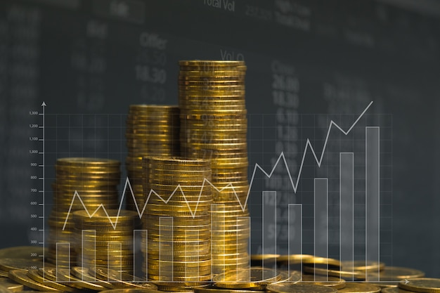 Double exposure of coin stack with stock market screen chart board and candle stick