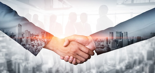 Double exposure image of business people handshake on city office building in background showing partnership success of business deal