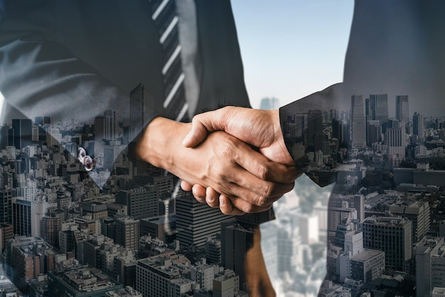 Double exposure image of business people handshake on city office building in showing partnership