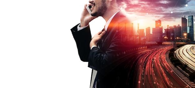 ビジネス通信ネットワーク技術コンセプトの二重露光画像-現代の街並みの背景にスマートフォンや携帯電話デバイスを使用しているビジネス