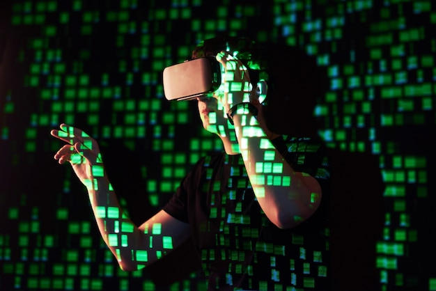 Двойное воздействие на кавказского человека и гарнитуру виртуальной реальности vr, предположительно, - это геймер или хакер, взламывающий код в защищенной сети или на сервере со строками кода, выделенными зеленым цветом.