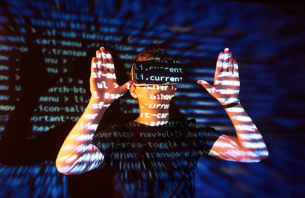 白人男性とバーチャルリアリティvrヘッドセットの二重露出は、ゲーマーまたはハッカーがコード行を使用して、安全なネットワークまたはサーバーにコードをクラックすることであると考えられます