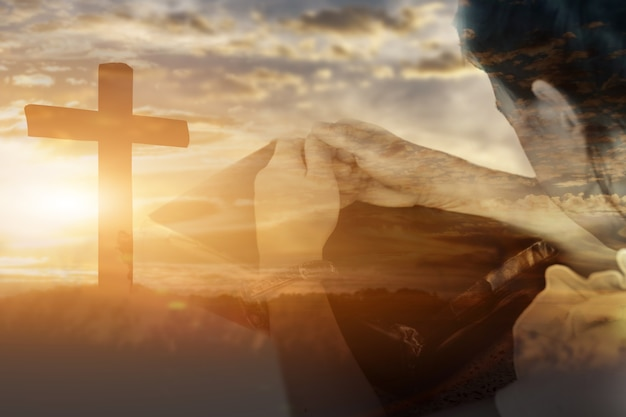 어린 소녀 걸쇠 손 숭배의 이중 노출과 일몰 배경에서 하나님을 찬양합니다. 기독교 종교 개념입니다.