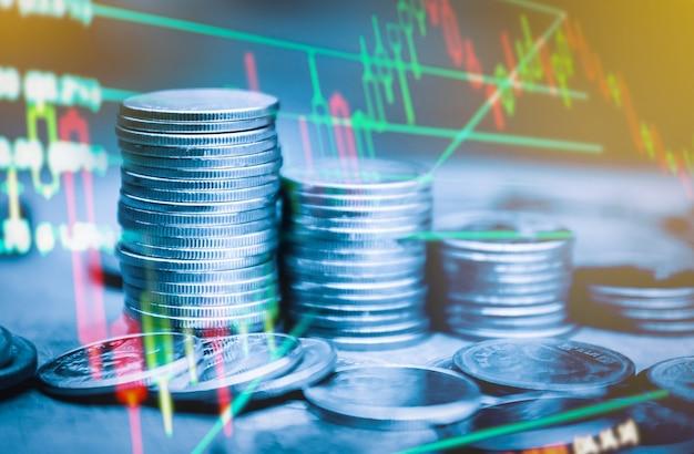 財務グラフの静止とゴールオフィスのコインの列の二重露光
