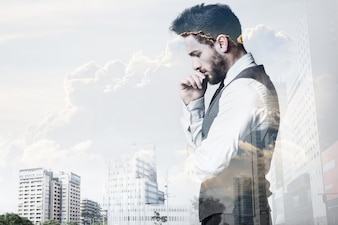 Double exposure of young businessman and city.