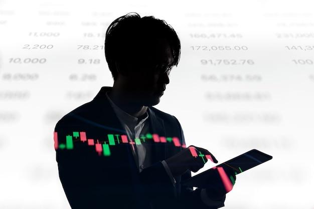 Двойная экспозиция силуэт планшета использования бизнесмена с прейскурантом фондовой биржи. концепция бизнеса и финансовой экономики. Premium Фотографии