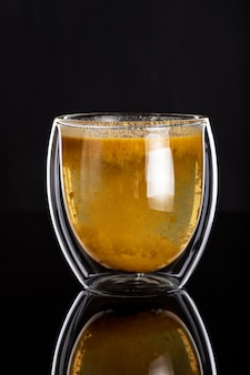 Double glass cup with homemade healthy sea-buckthorn tea on black surface