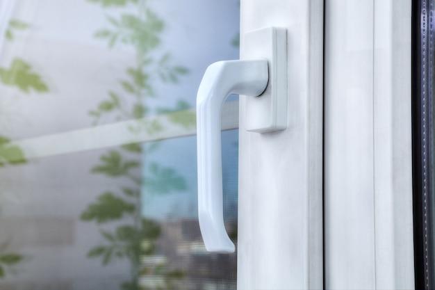 Двойное белое виниловое окно из алюминиевого профиля и пластика с двойным остеклением и москитной сеткой.