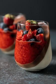 Двухслойный ванильно-шоколадный десерт панна котта с клубничным пюре, свежей черникой и клубникой