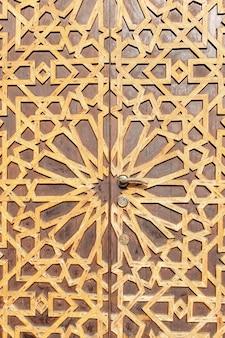 Двойная старая деревянная дверь с орнаментом внешний вид