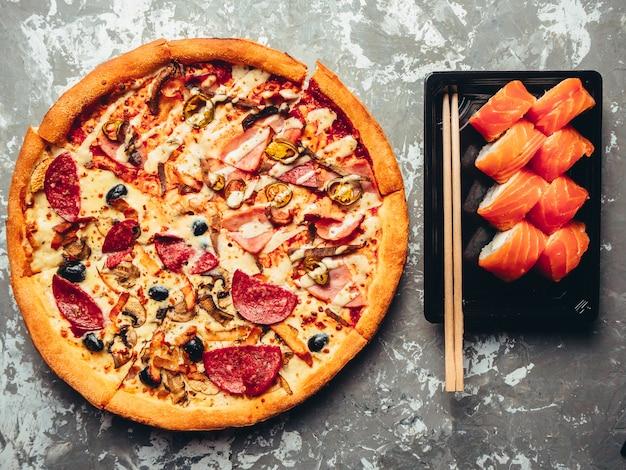 Двойная пицца и роллы филадельфия на черном белом